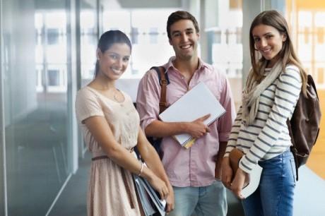 Portrait of smiling university students in corridor